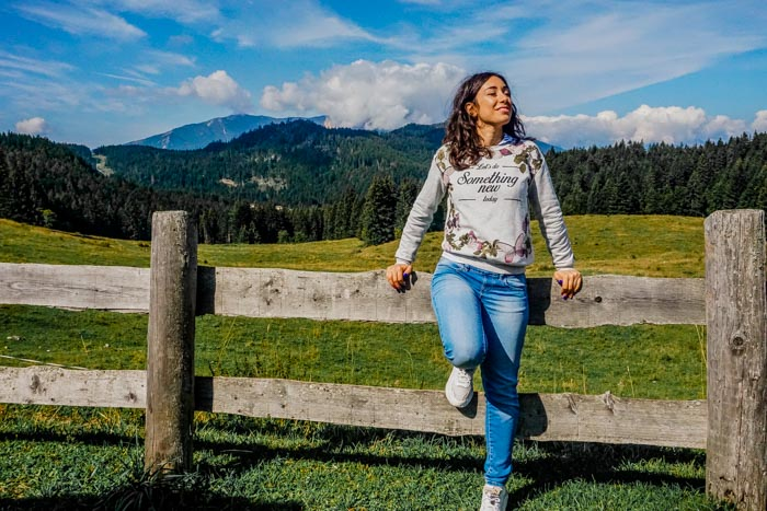 ragazza su un recinto di legno con dietro la natura